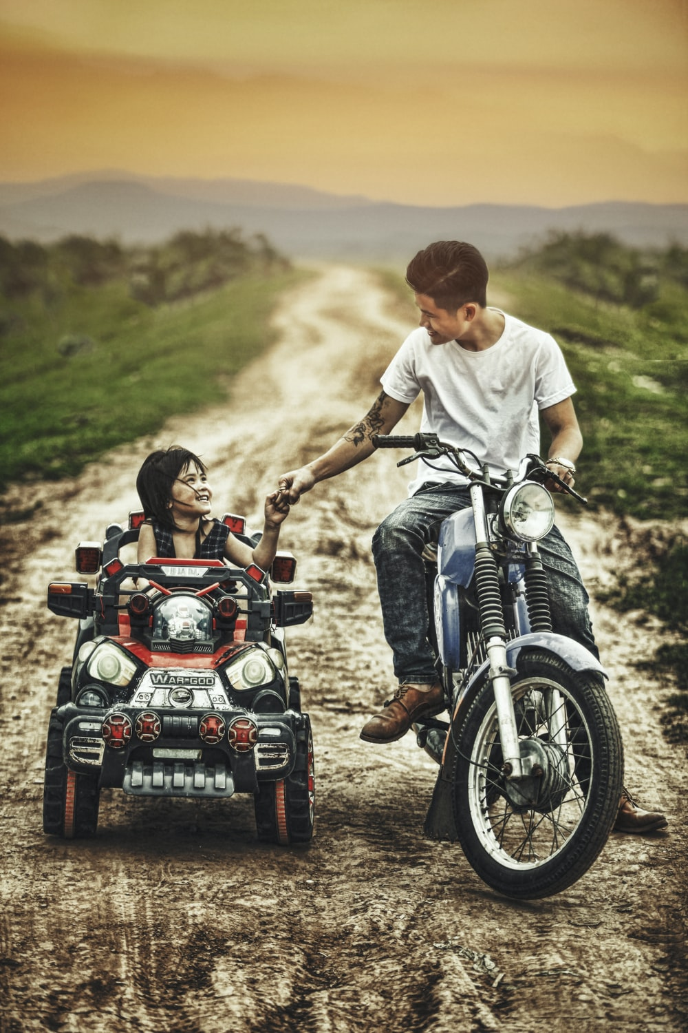 man riding motorcycle and toddler on a toy car in a road during daytime