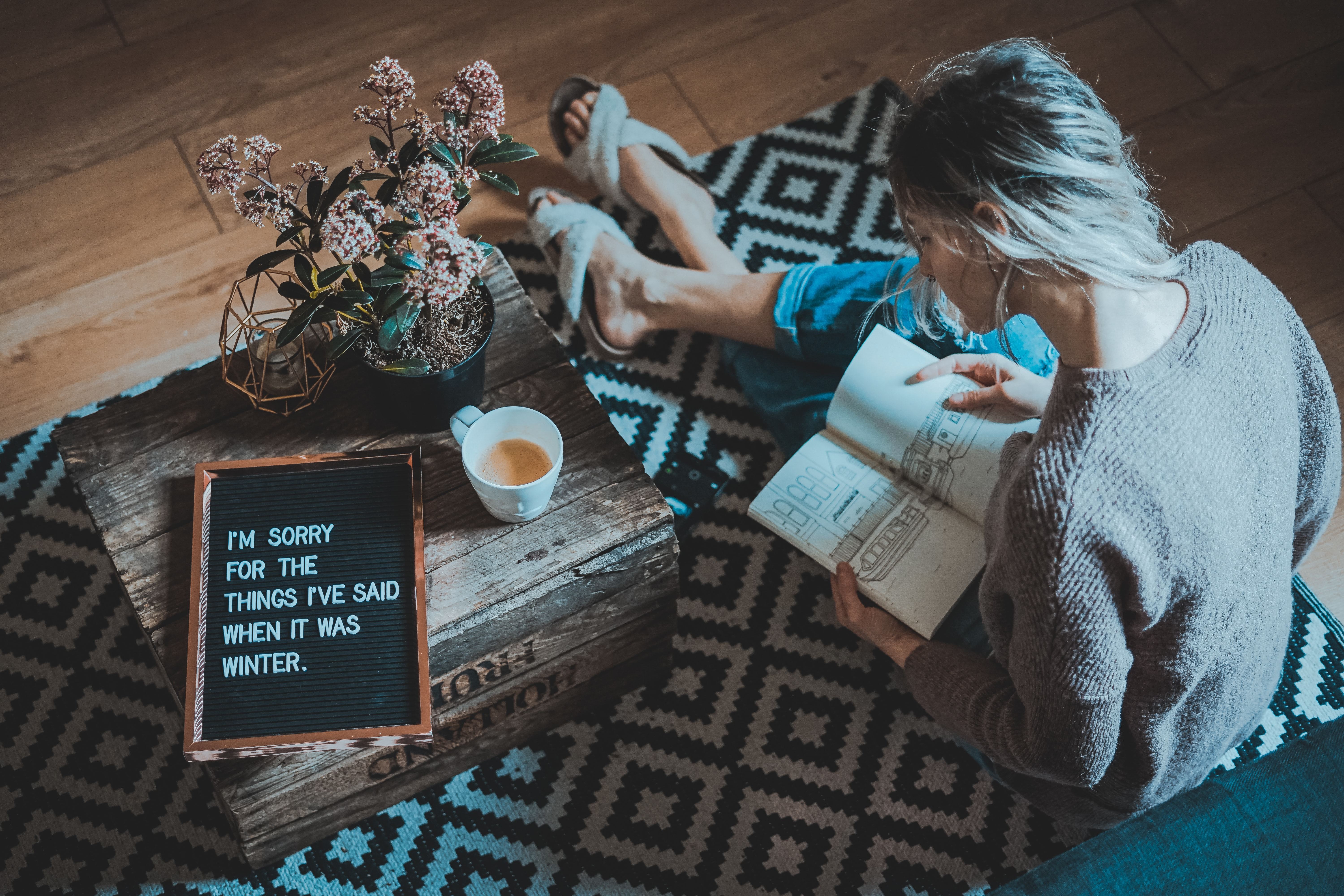 woman sitting on rug while reading book near coffee table