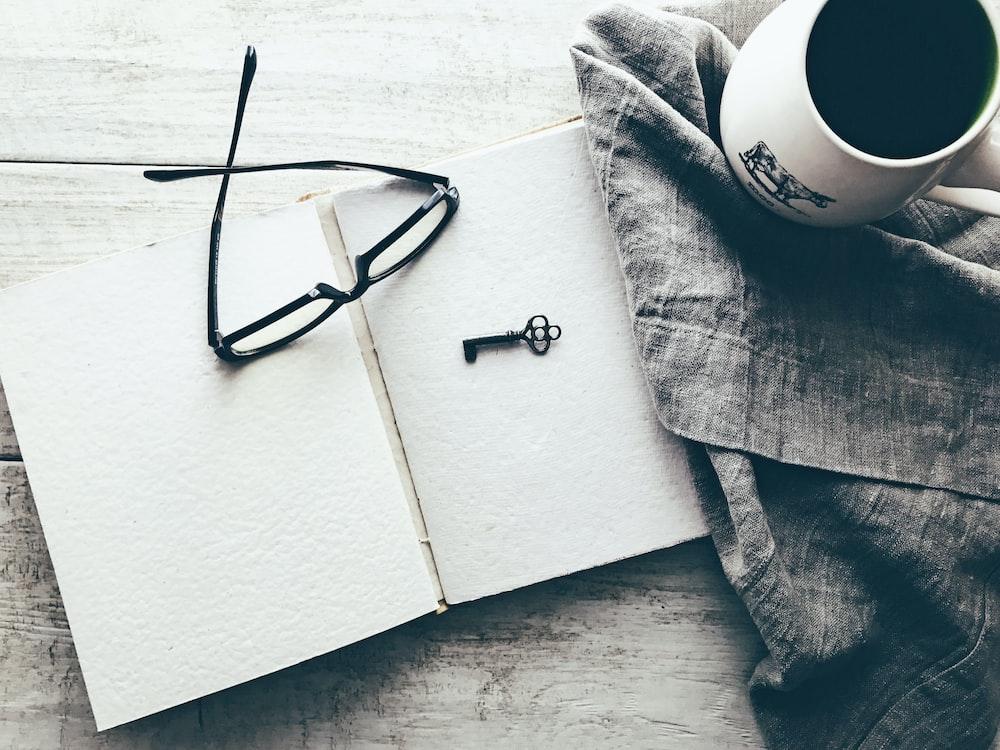 eyeglasses and skeleton key on white book