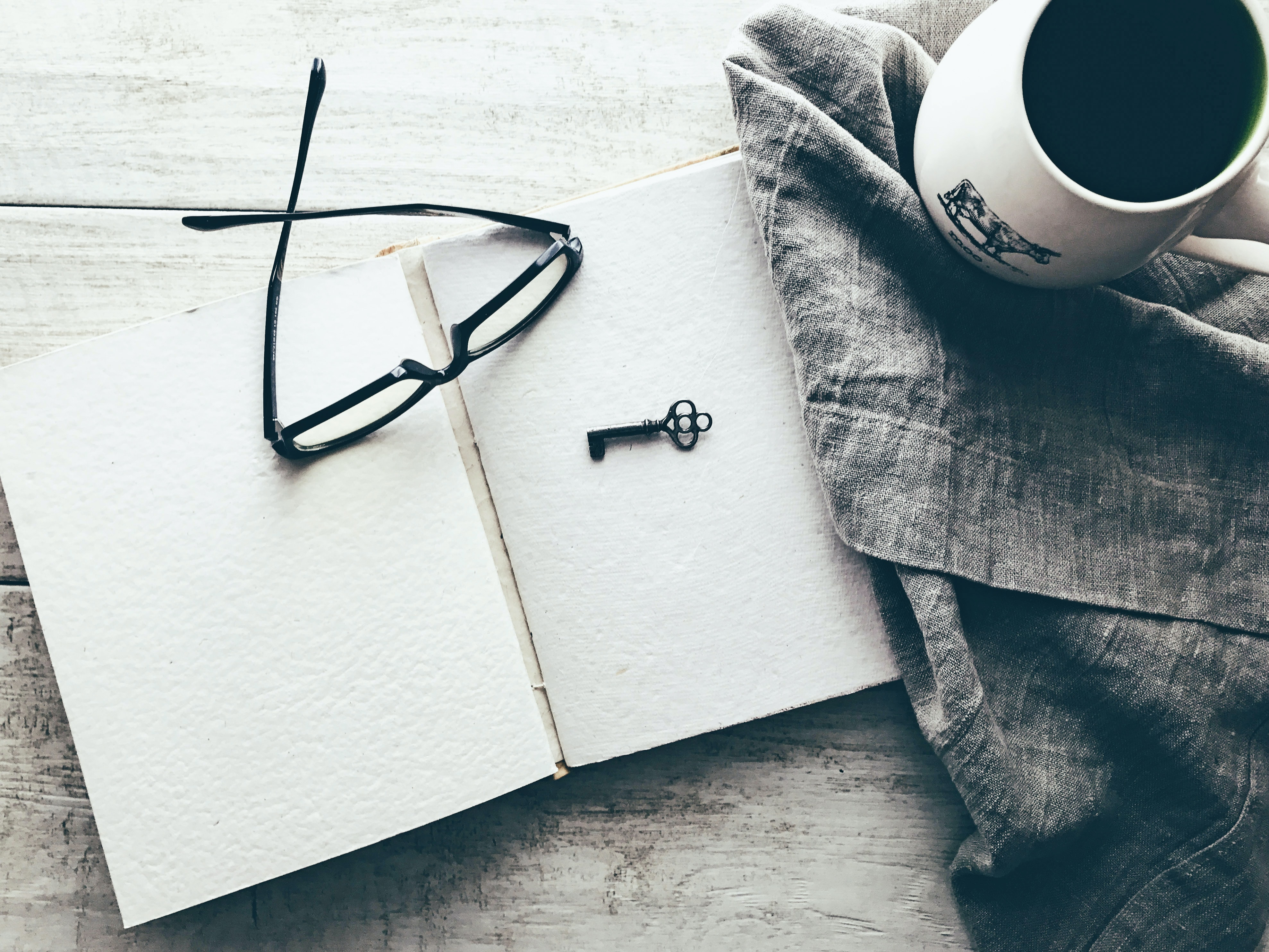 eyeglasses and skeleton key on white book