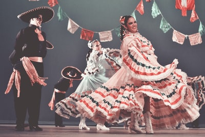 dancing women and men on stage mariachi teams background