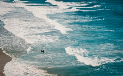 two persons walking on seashore seascape zoom background
