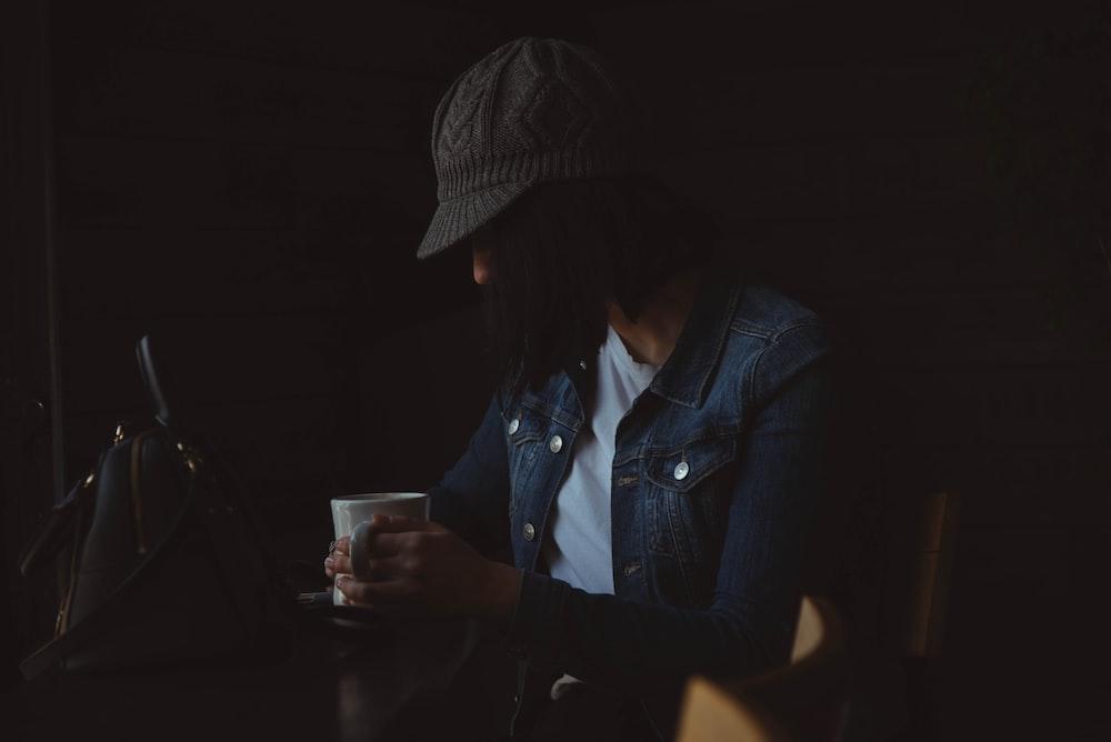 person sitting while holding mug
