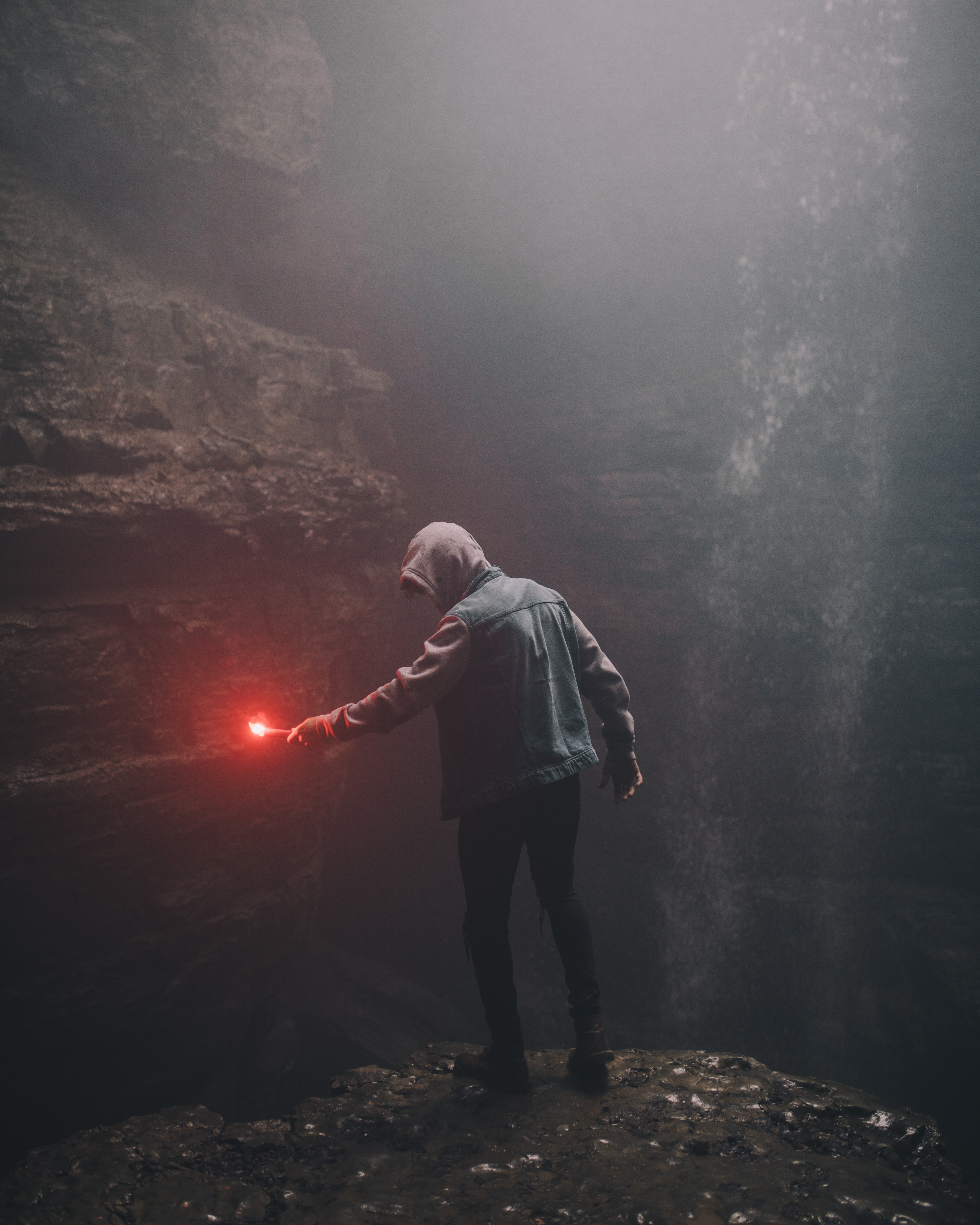 man on edge of cliff holding signal flare light