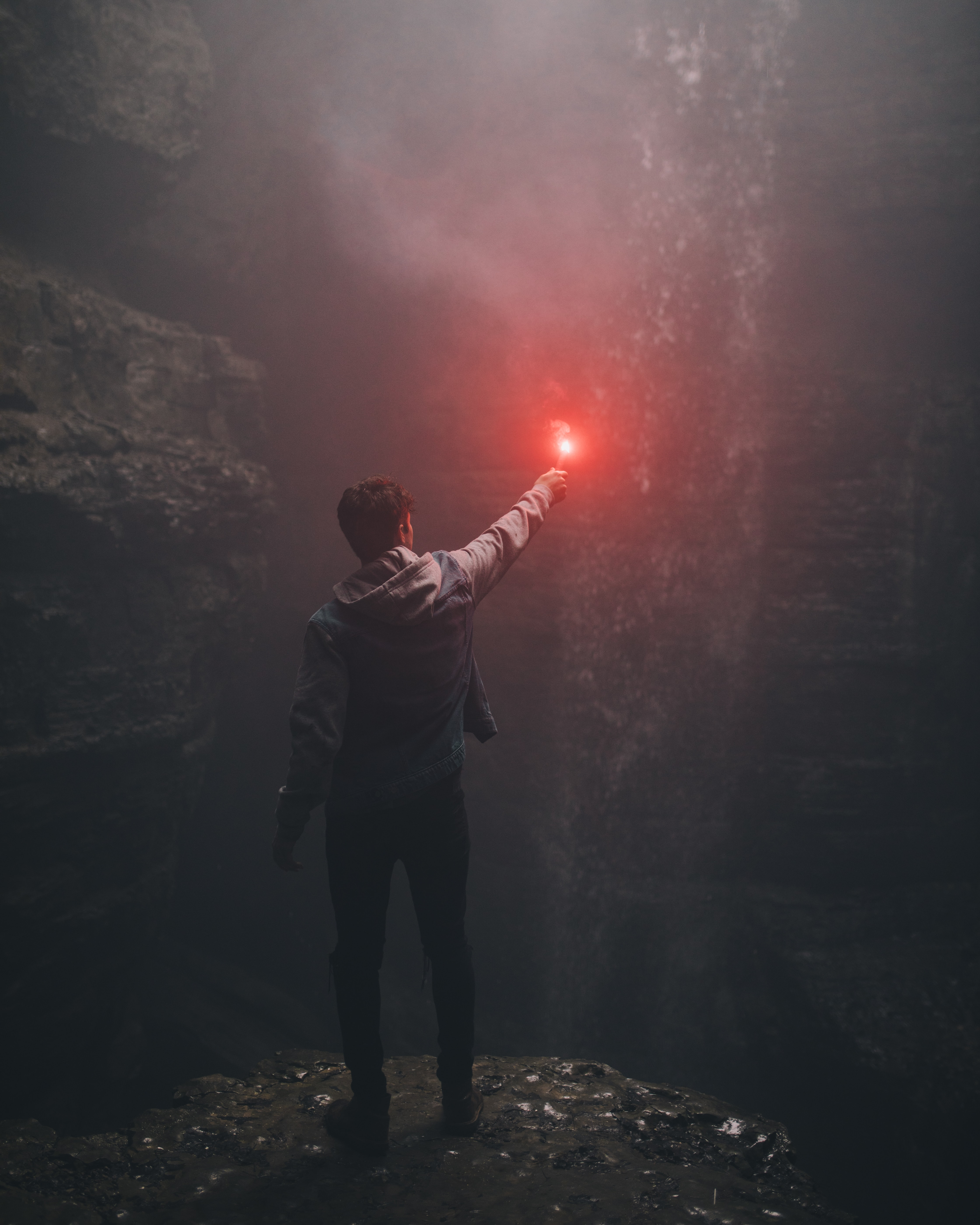 man lighting up flare in cave