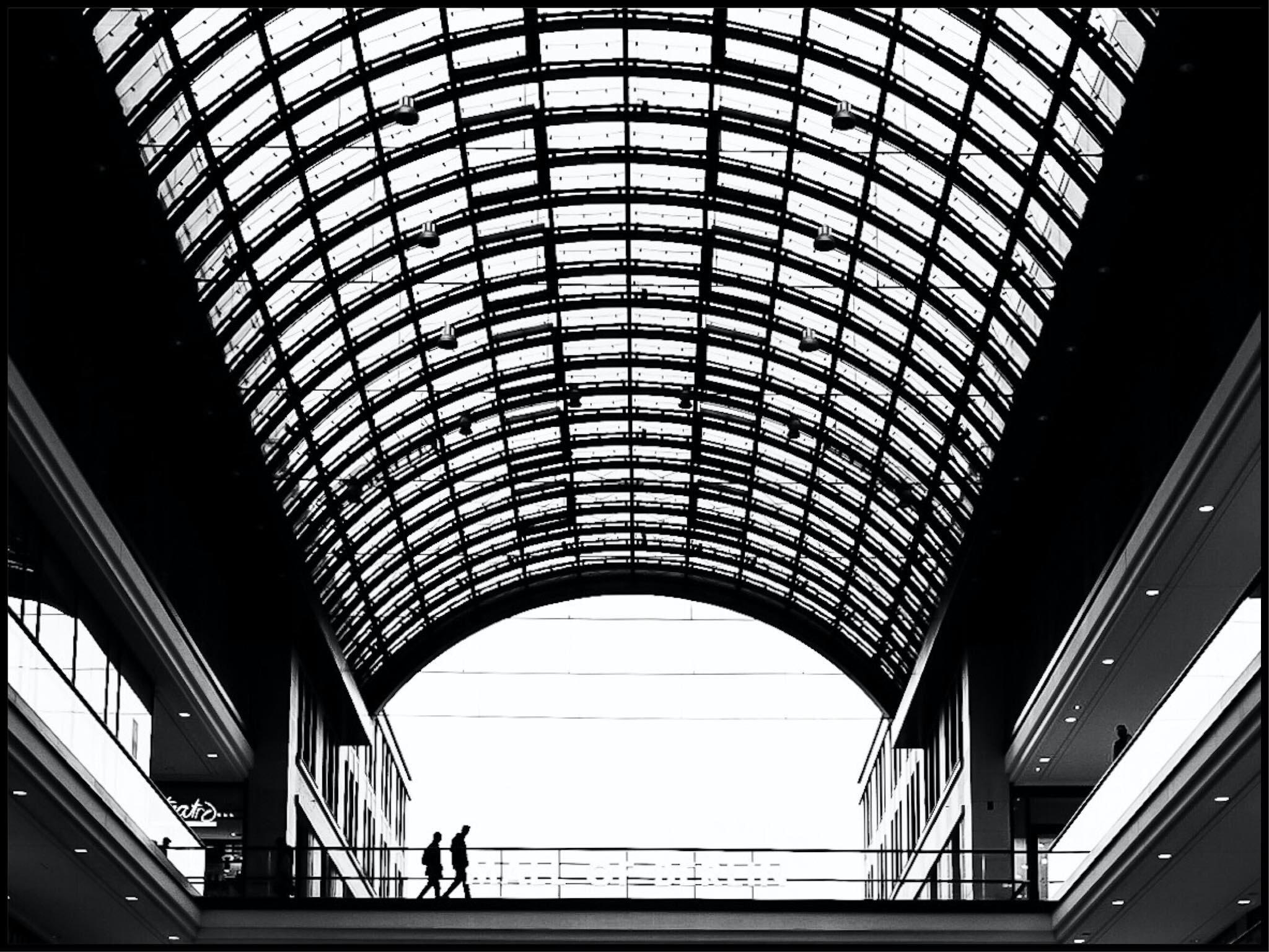 two people walking inside building