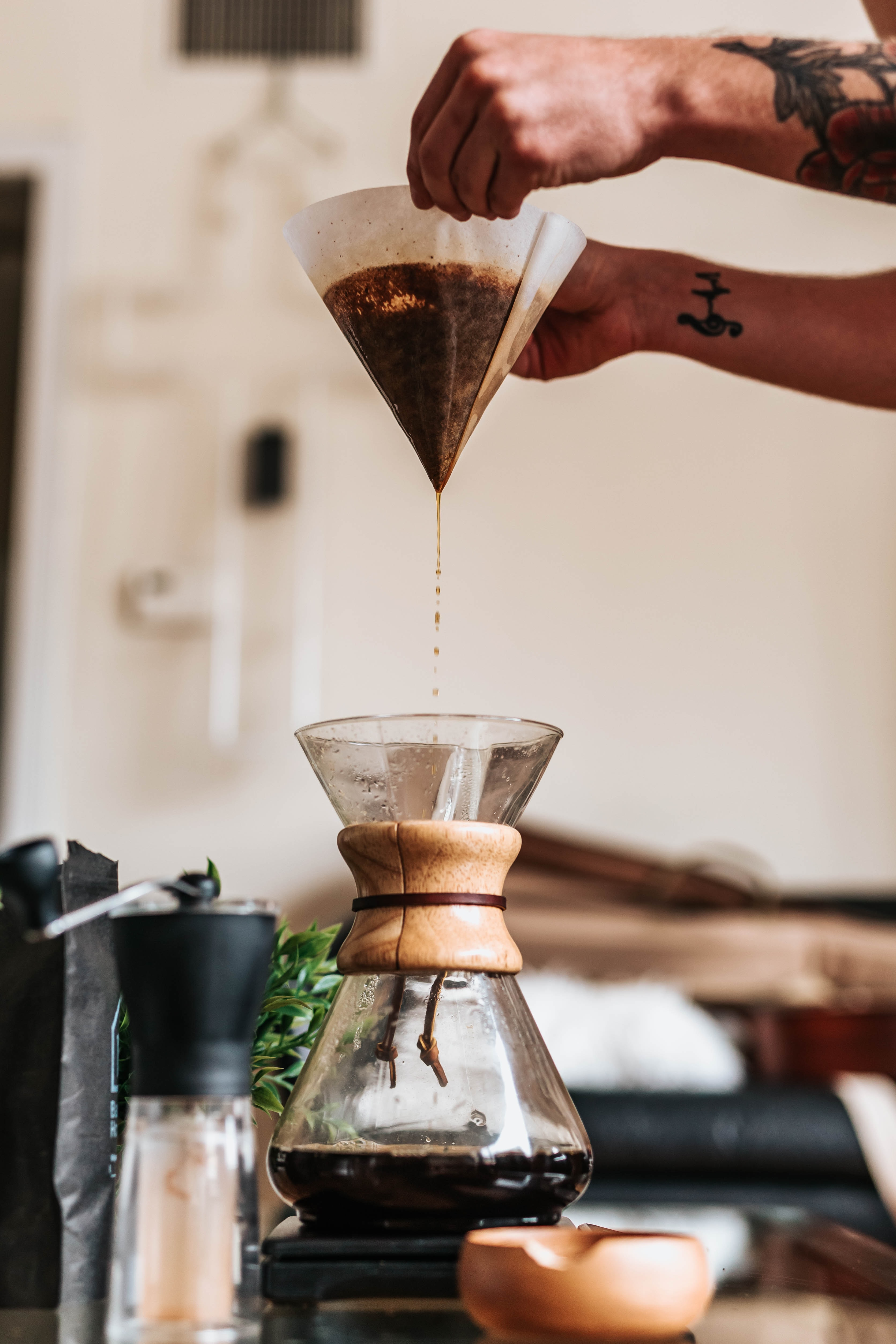 person filtering coffee in funnel
