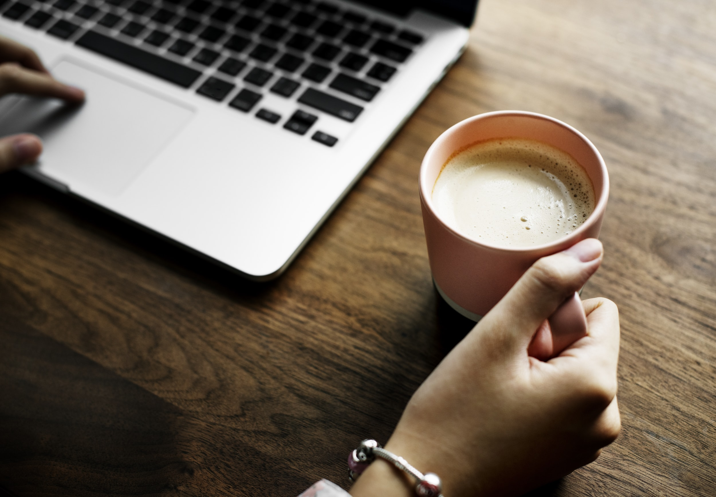 person holding pink ceramic mug beside MacBook Pro