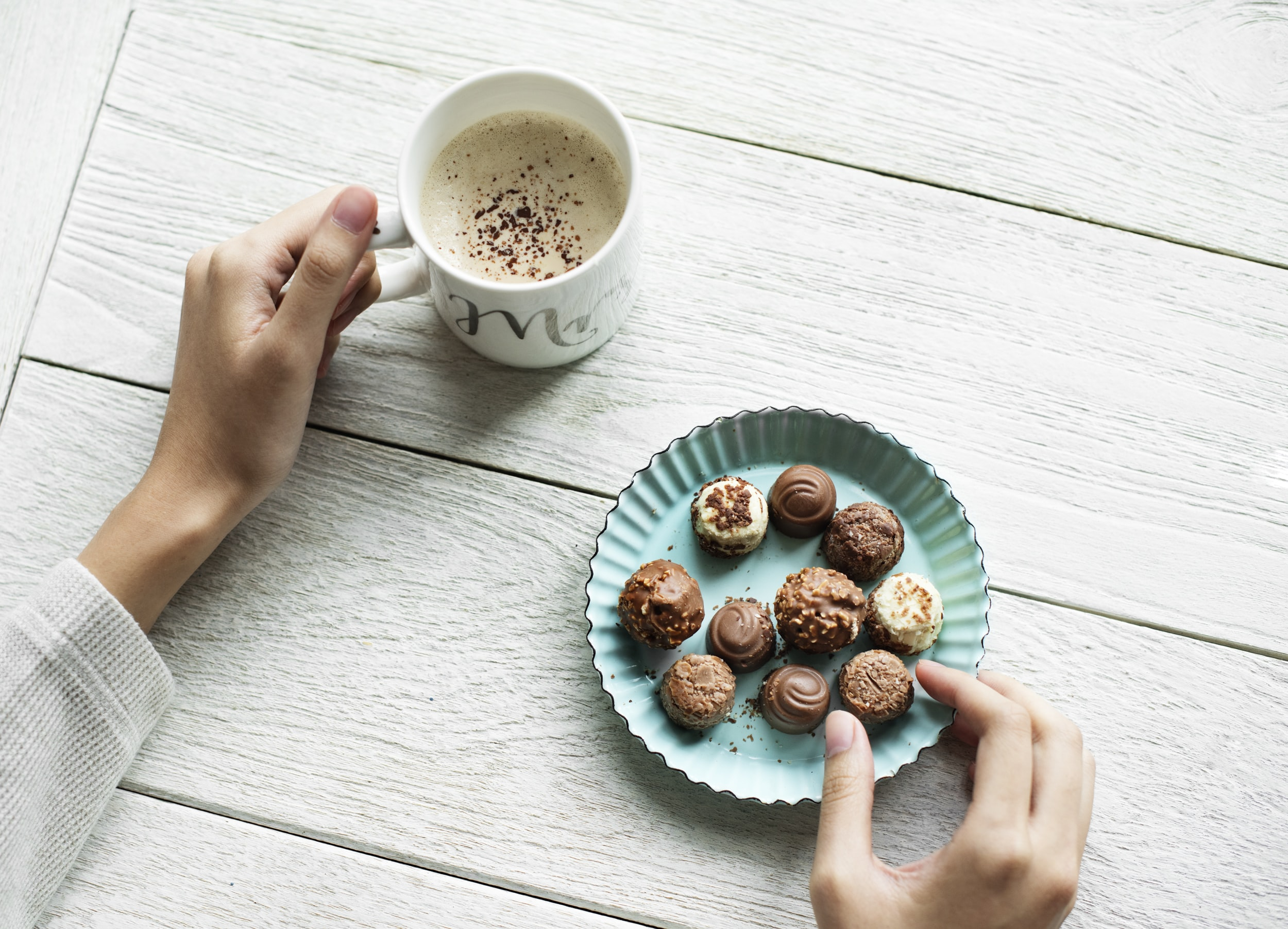 person picking up chocolate on saucer and holding mug filled with beverage