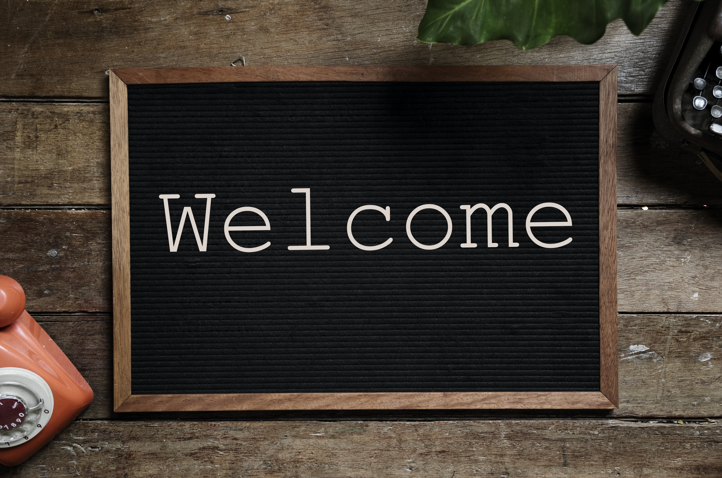 black and brown wooden welcome board near orange telephone
