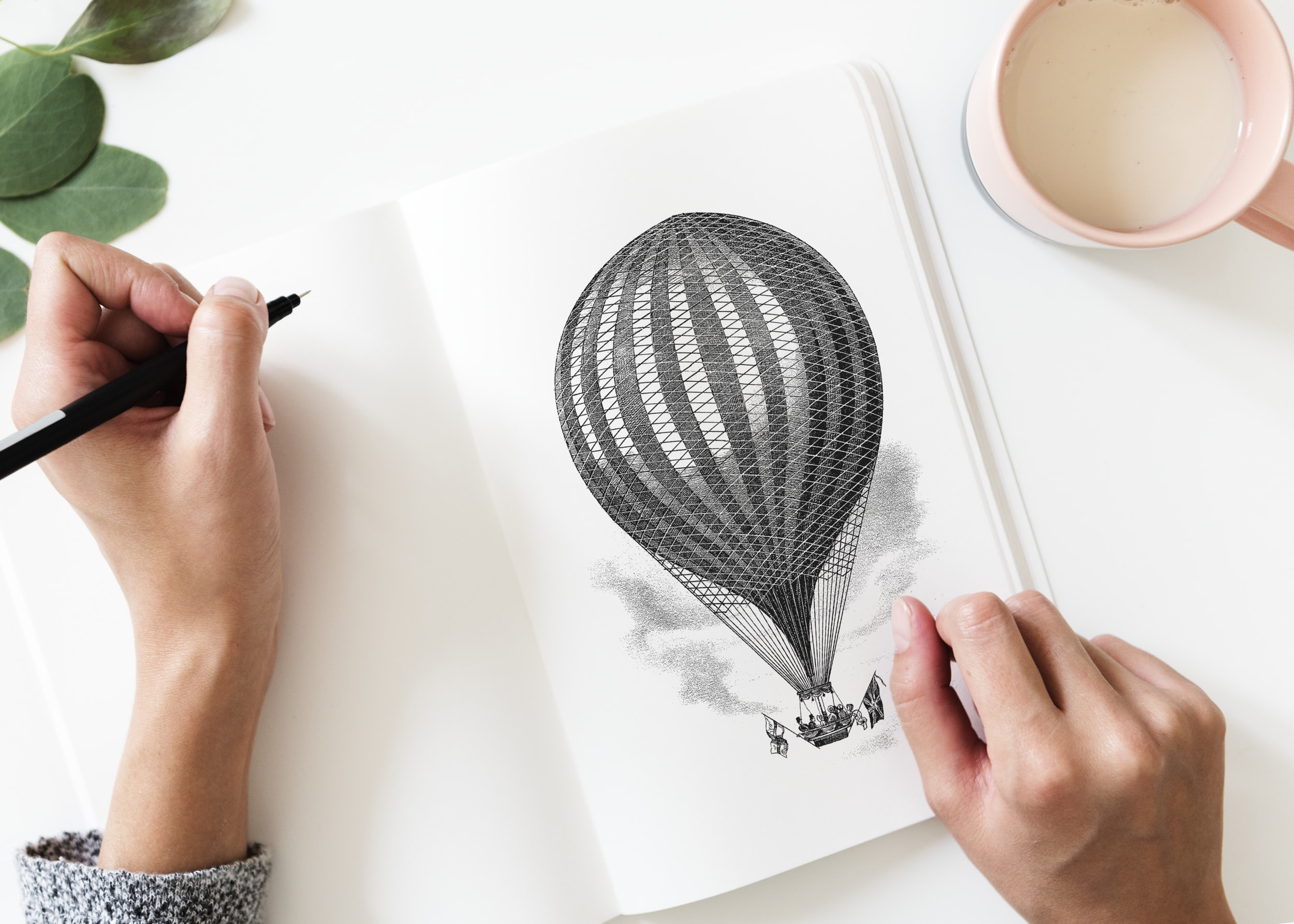 flay-lay photography of person sketching hot air balloon