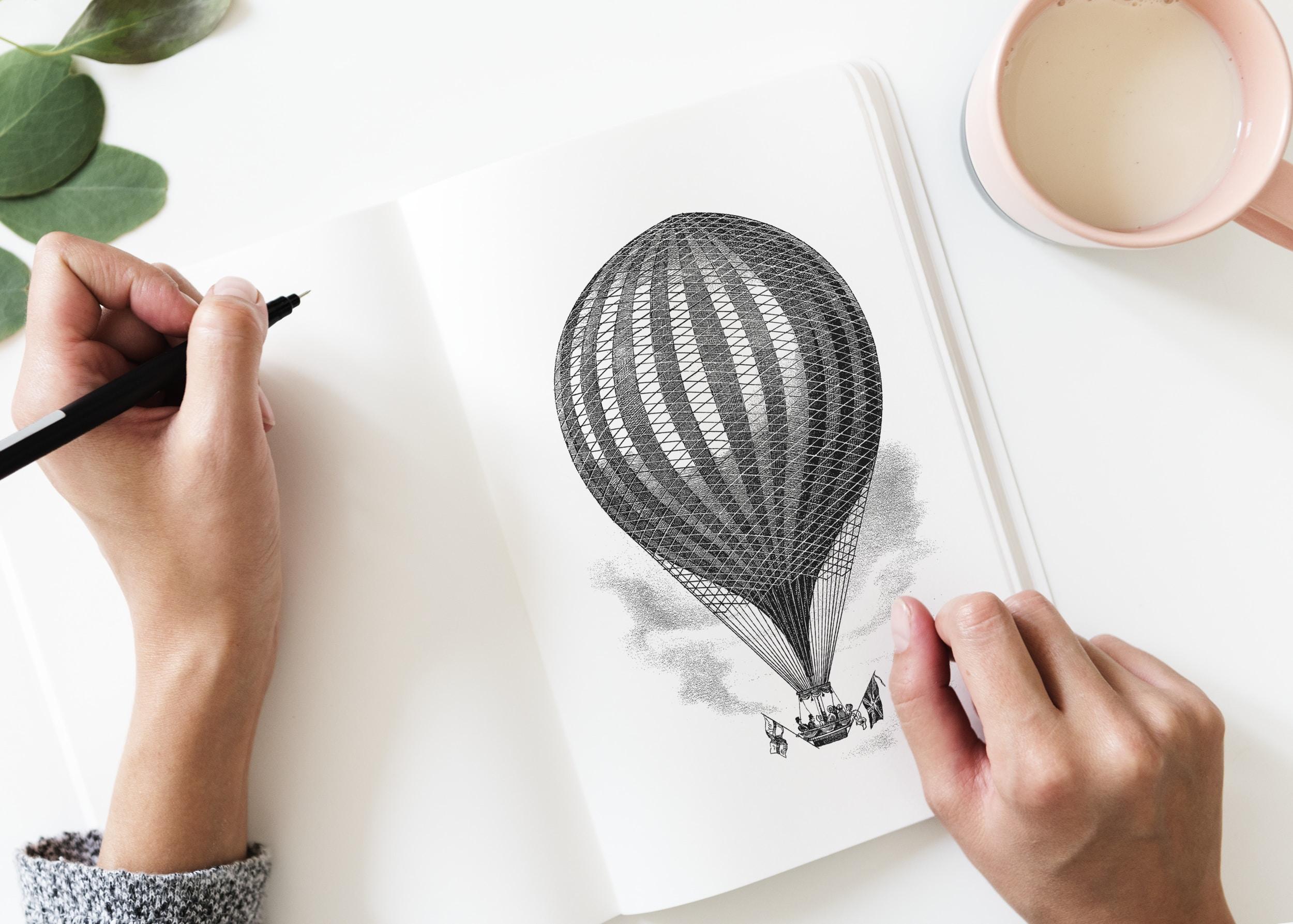 flay-lay photography of person sketching hot air balloon