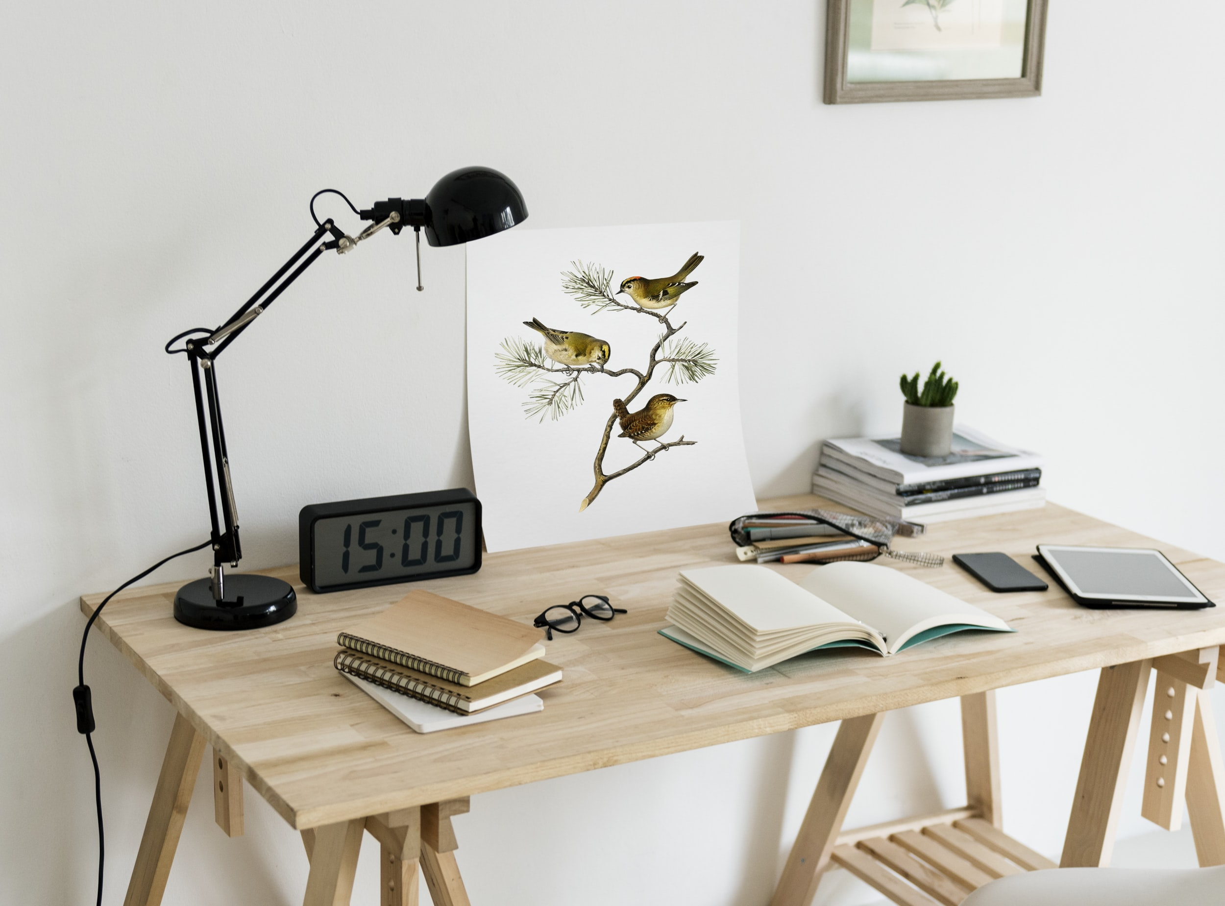 book, iPad, alarm clock, and desk lamp on table