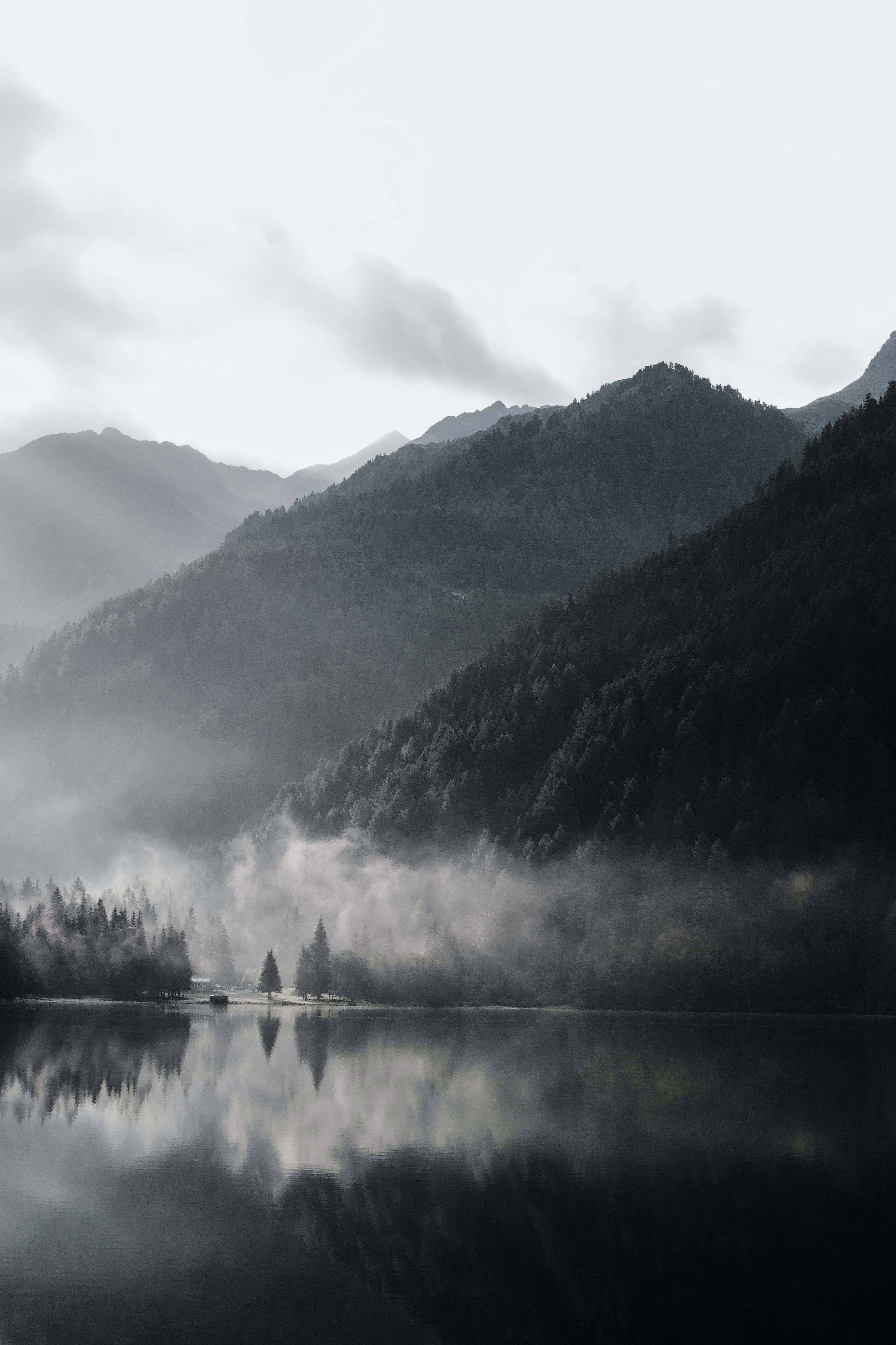 grayscale photography of mountain range with body of water