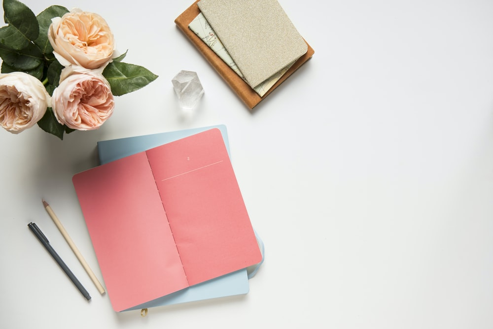 pink covered book in top view photography