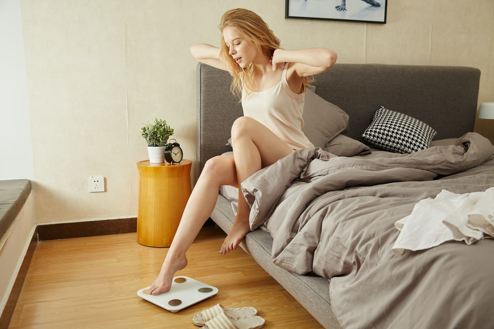 woman stretching sitting on bed inside bedroom