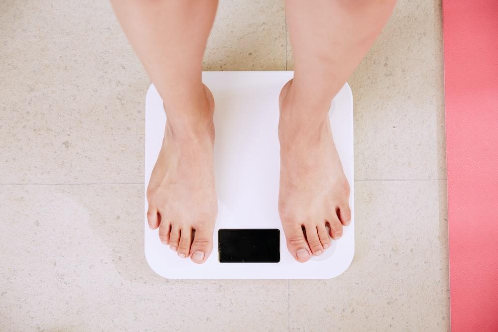 白いデジタル体重計の上に立っている人