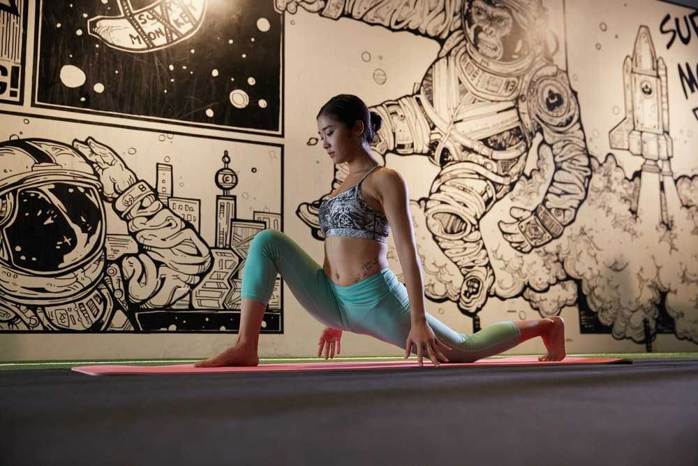 woman doing yoga beside mural wall