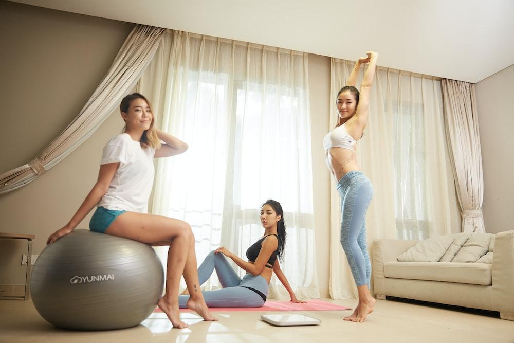 three women doing exercise inside gray room