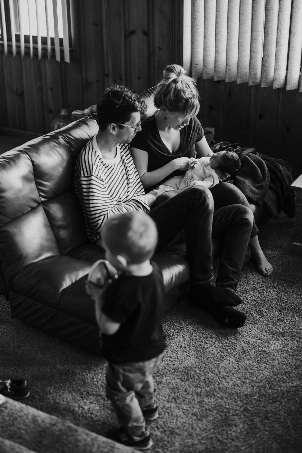 grayscale man and woman sitting on couch carrying baby
