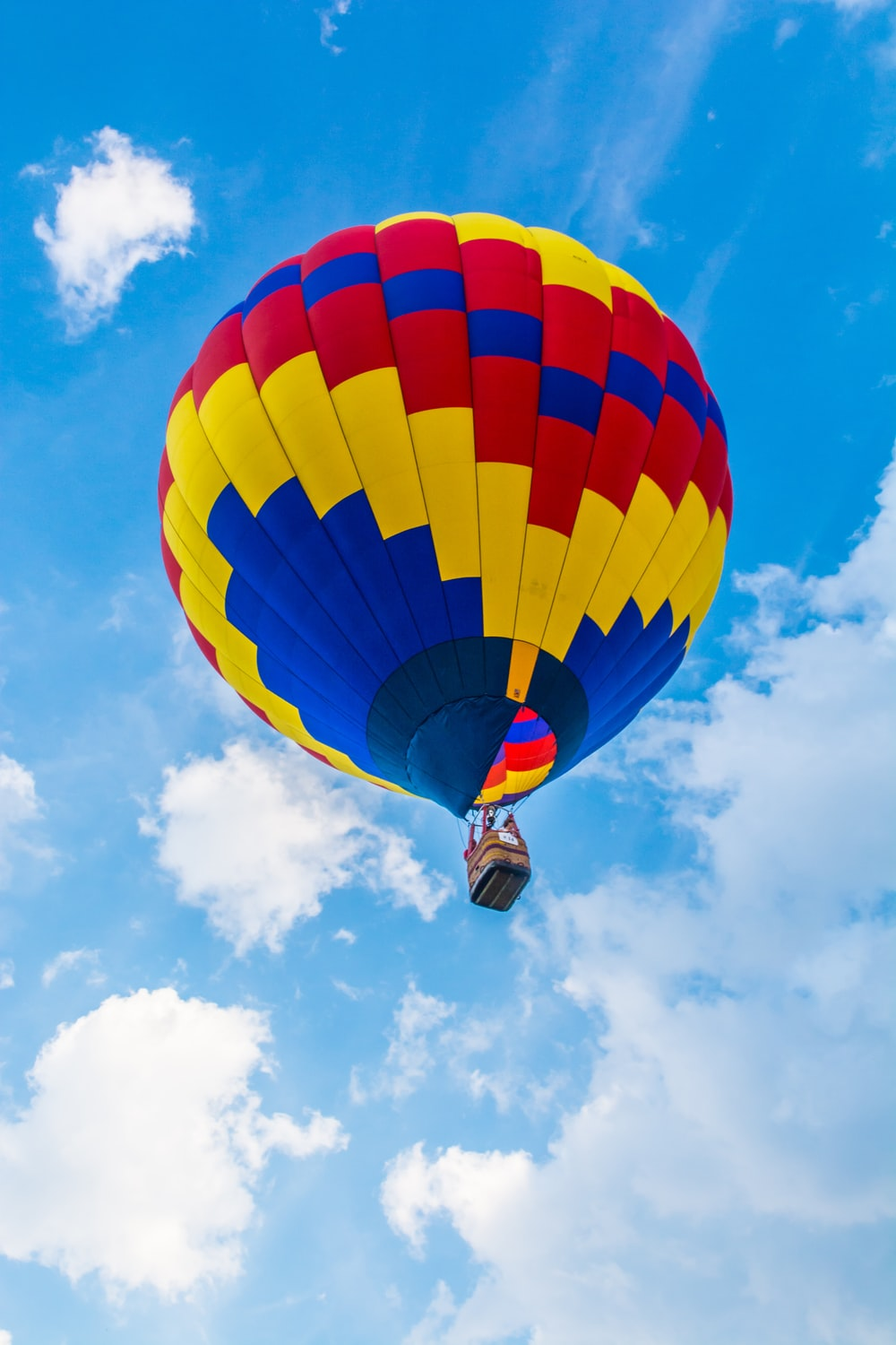 yellow, red, and blue hot air balloon flying during daytime