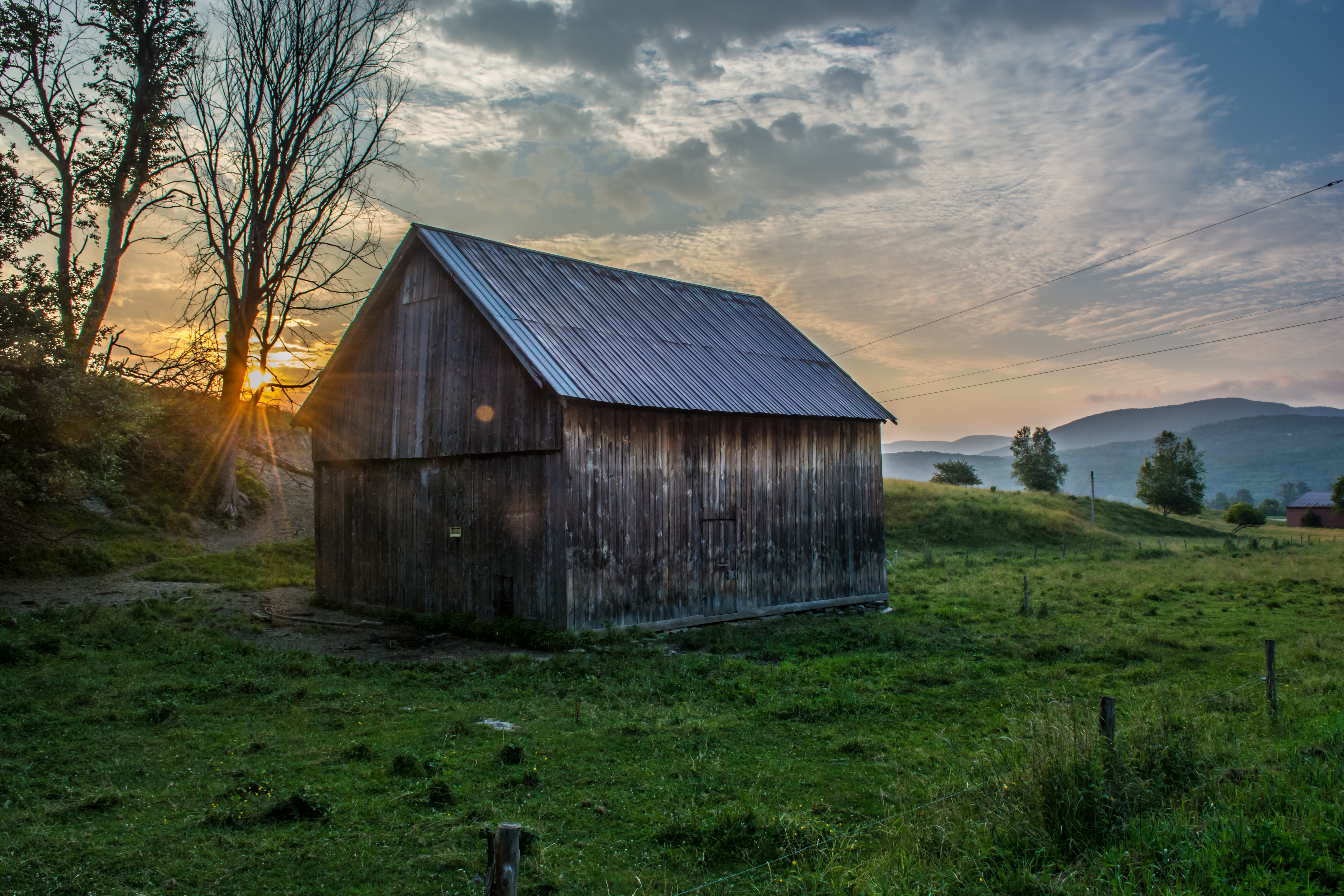 brown wooden shed surrounded by green grass