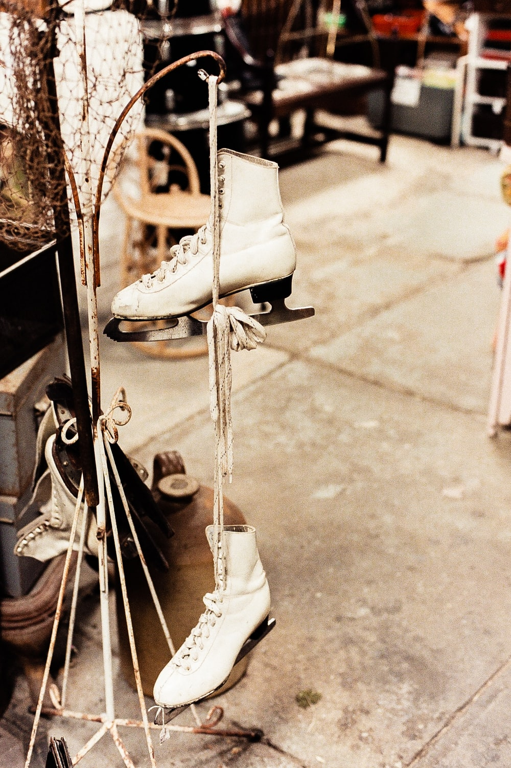 pair of white figures skates hanging on coat stand