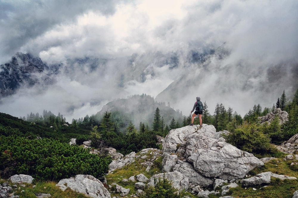 person standing on gray boulder looking at mountains