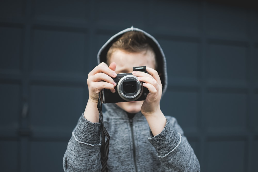 person in grey hoodie holding up camera over face