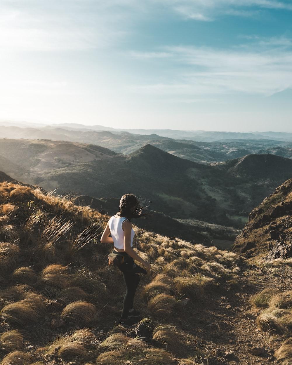 woman walking on brown mountain