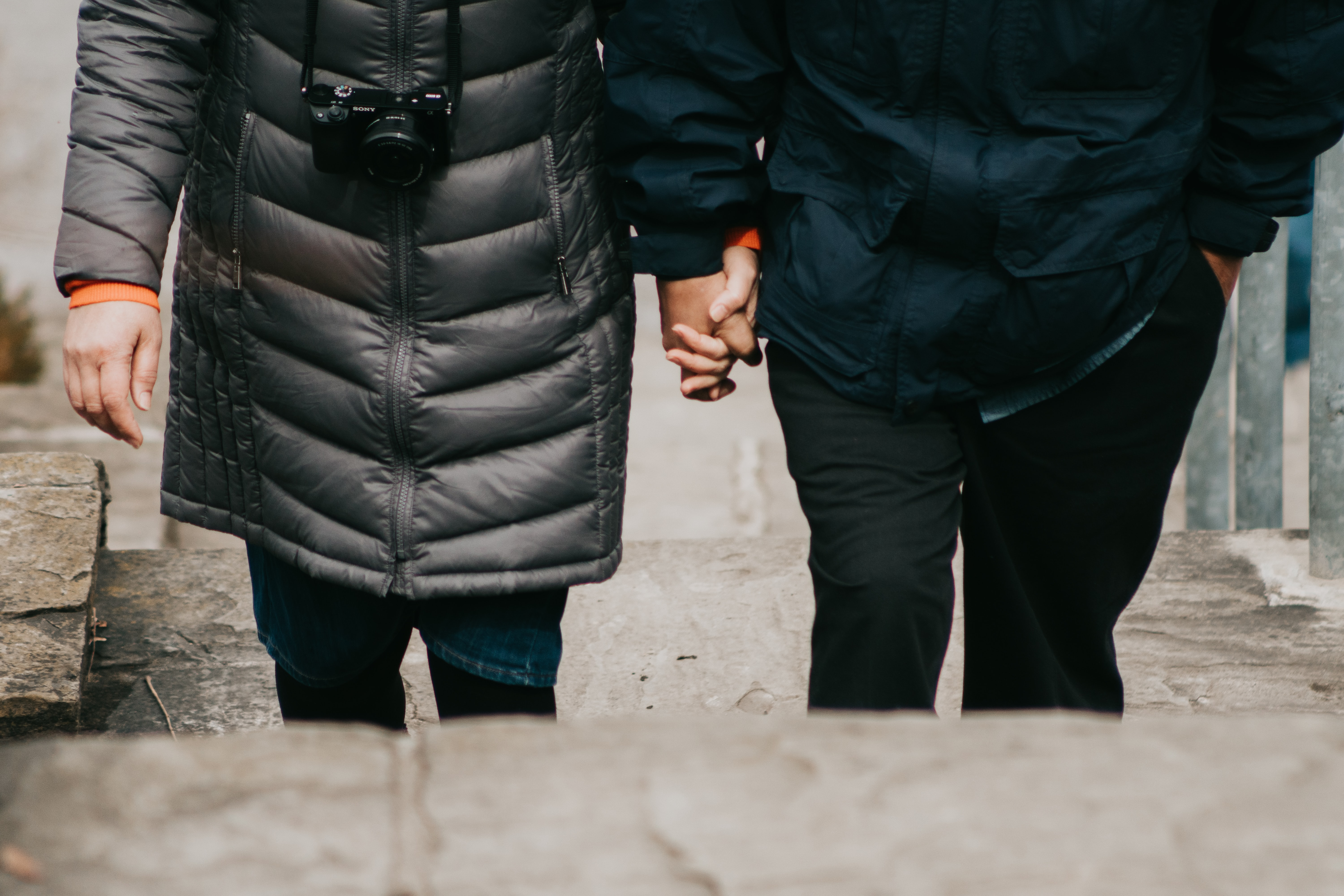 man and woman holding hands walking on stairs