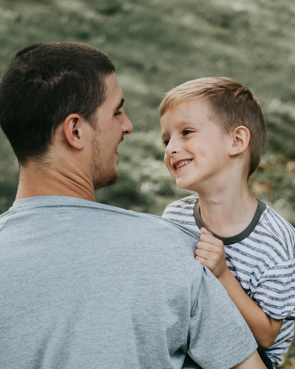 man carrying boy both smiling