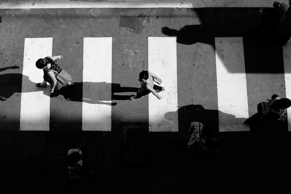 grayscale photo of people crossing pedestrian street