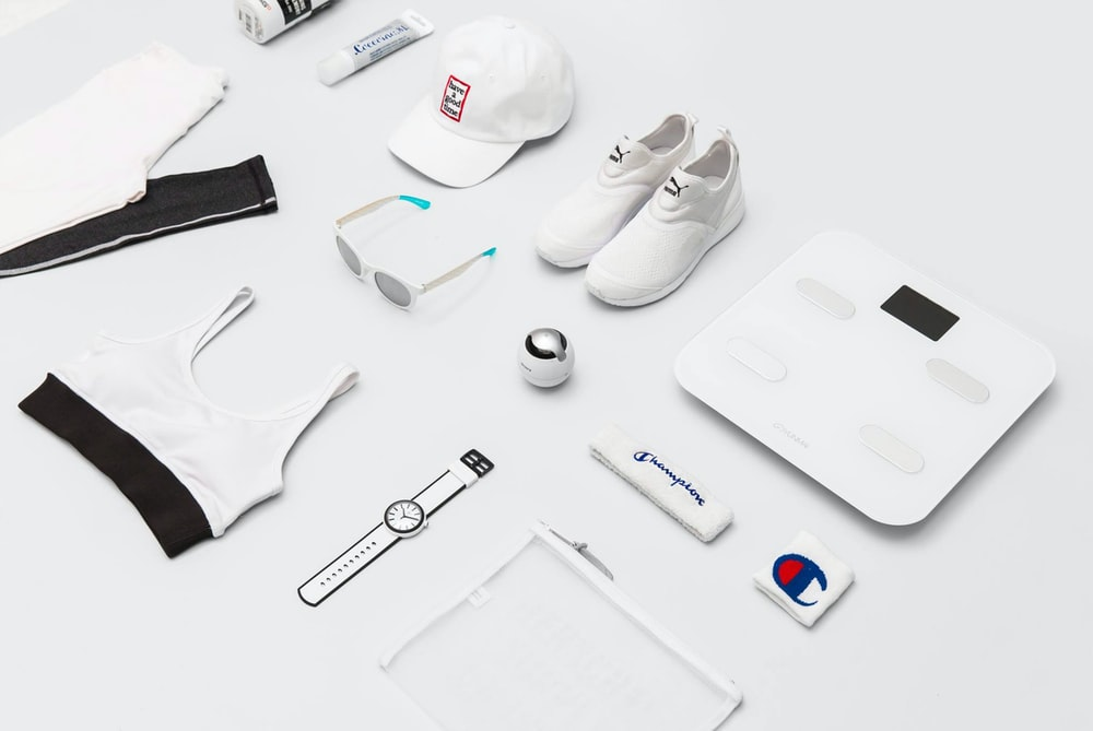 flat lay photography of shoes, sunglasses, cap, pants, and sport brassiere