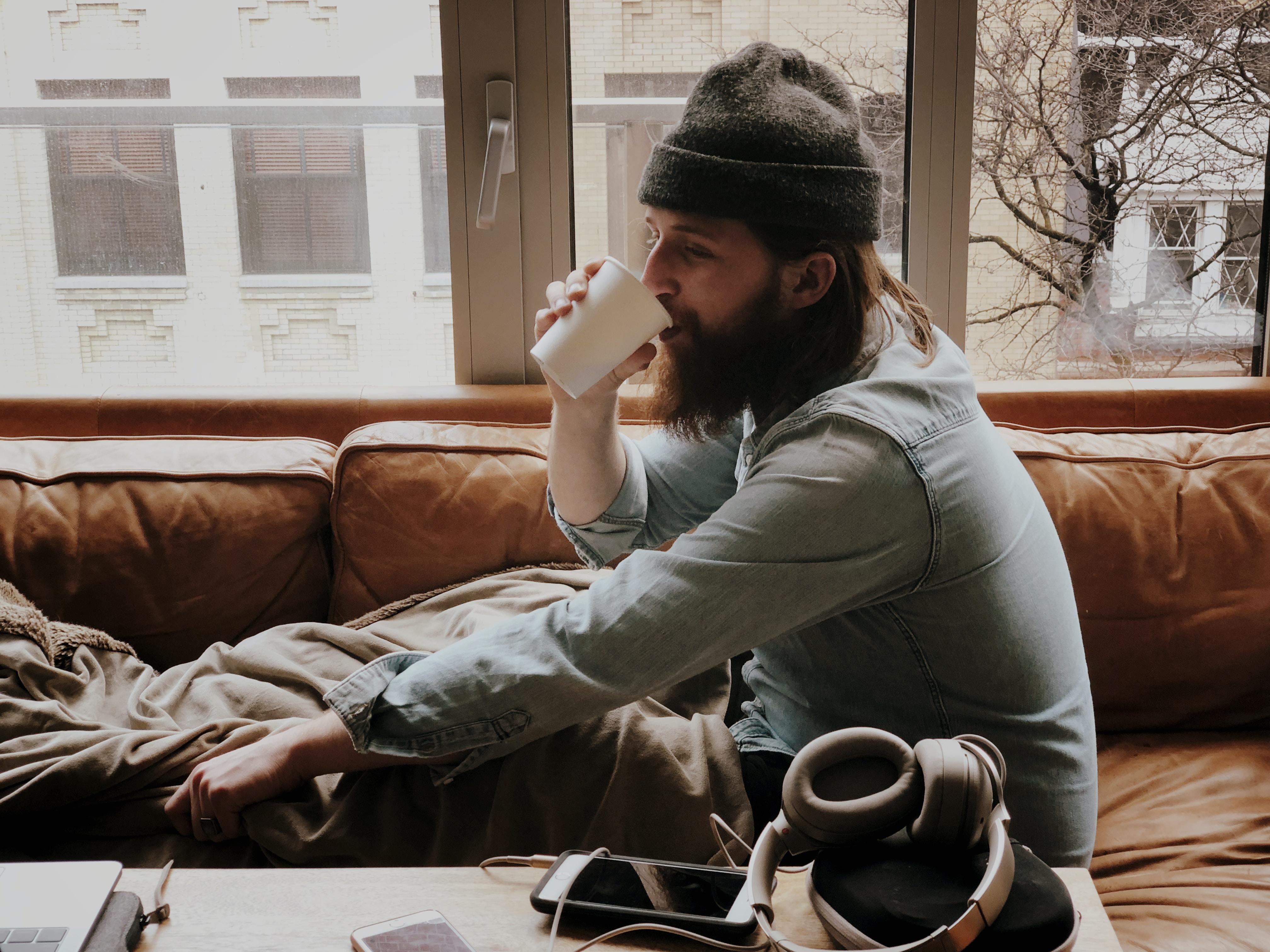man sitting on sofa while drinking