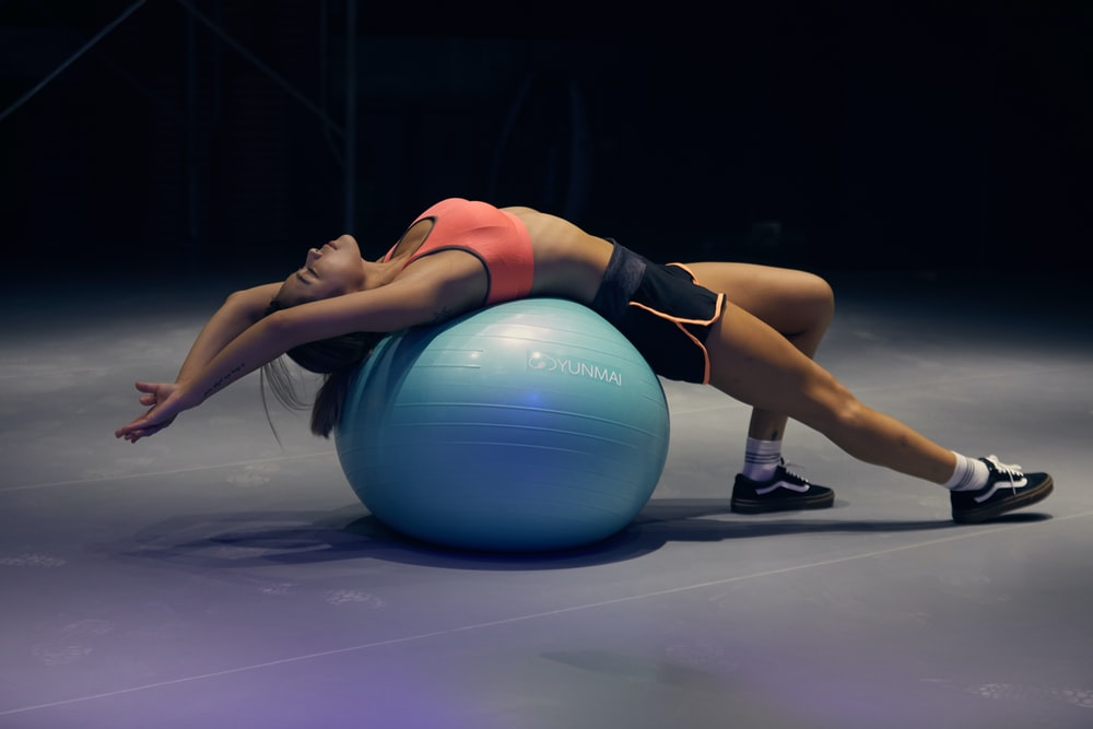 woman doing yoga on stability ball