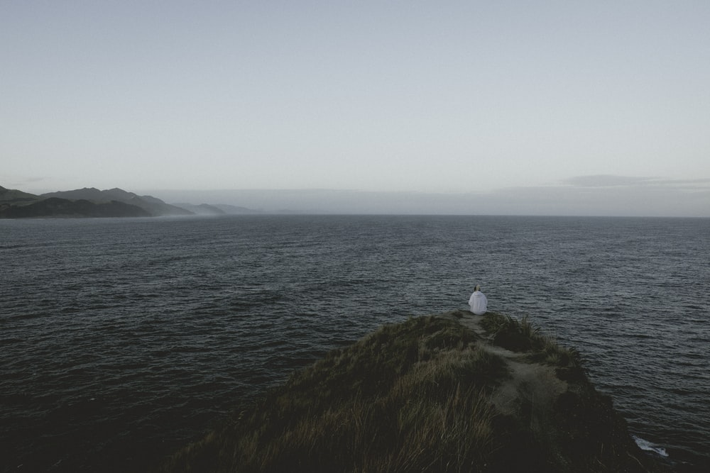 person sitting on a cliff beside a body of water