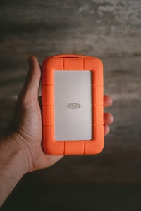 person holding rectangular orange and gray plastic case