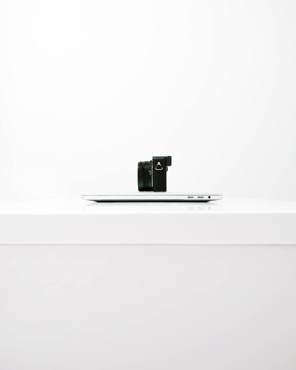 black mirrorless camera on top of MacBook