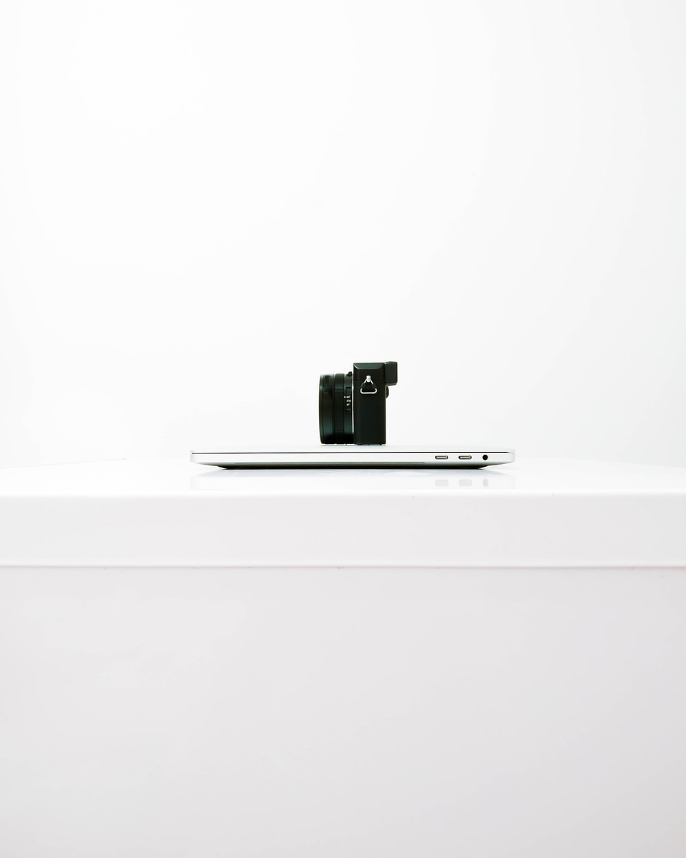 black mirrorless camera on top of MacBook