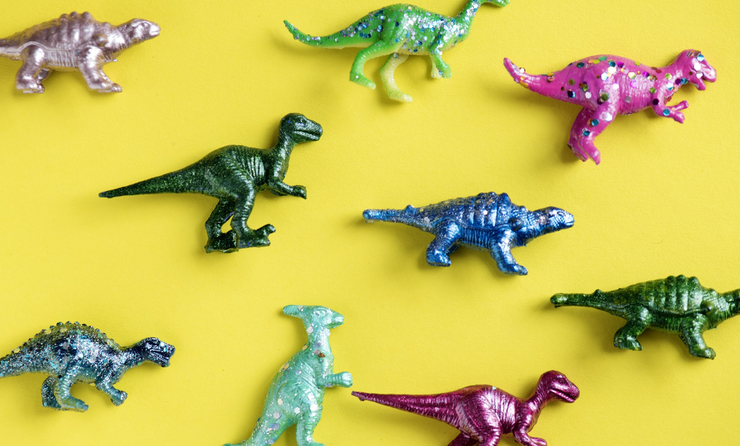 flat-lay photography of dinosaur figurines on yellow surface