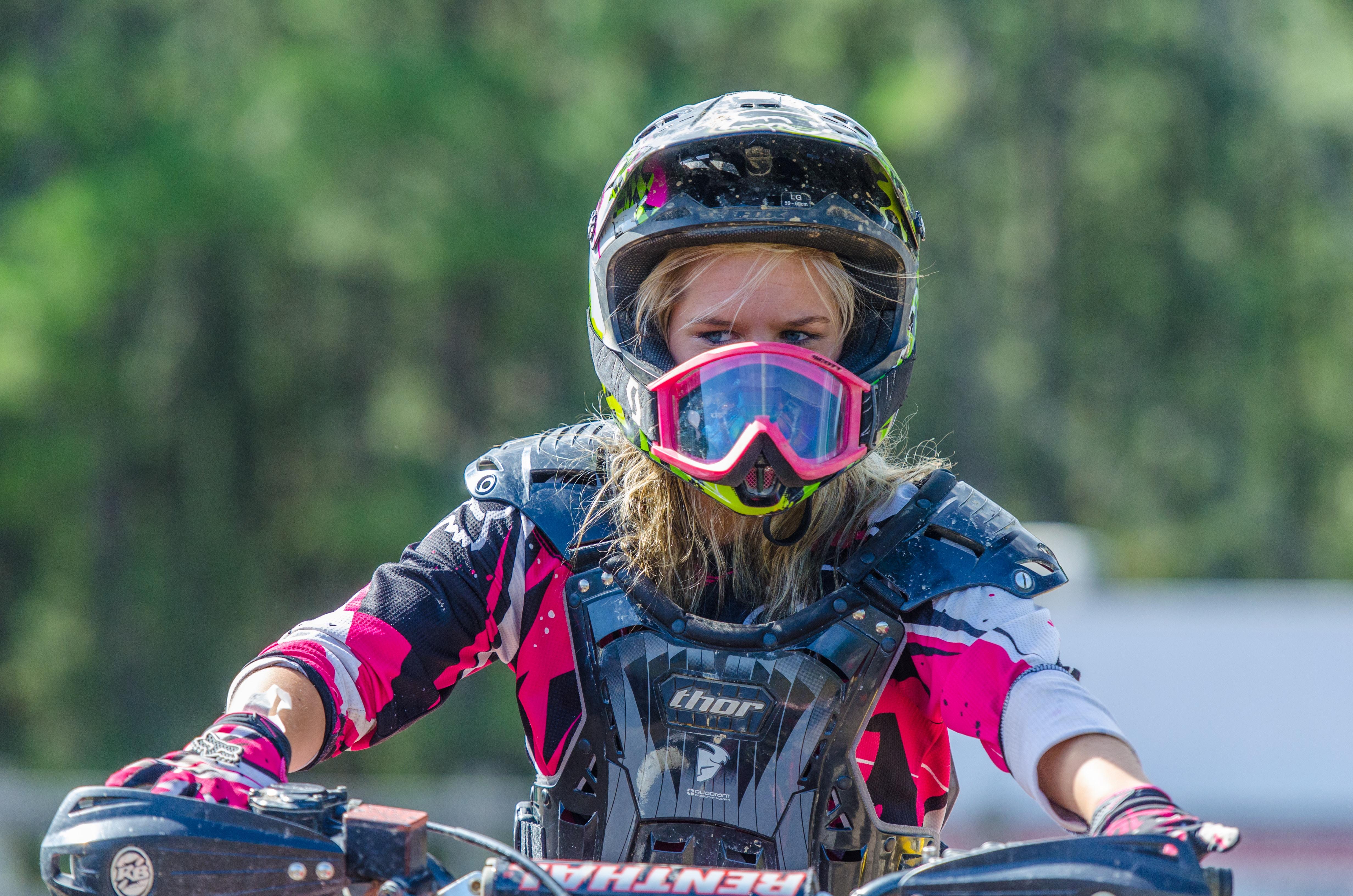 woman riding motocross dirt bike at daytime