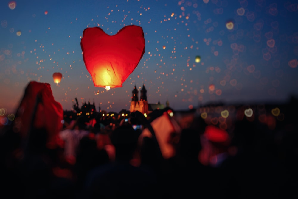 crowd of people flying heart lanterns in the sky