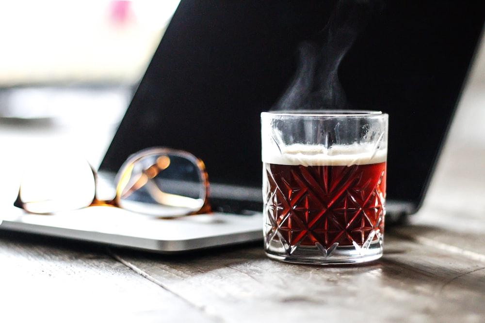 red liquid inside glass near eyeglasses on top of laptop