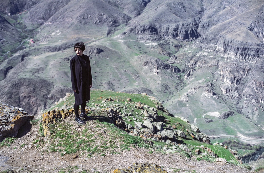 woman standing on cliff wearing black suit