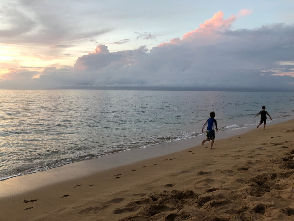 two children running at the beach shore during sunset