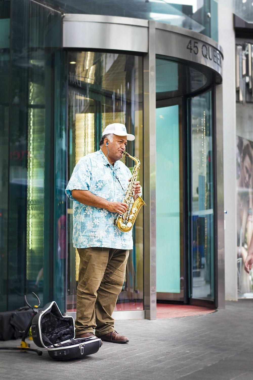 man standing playing saxophone