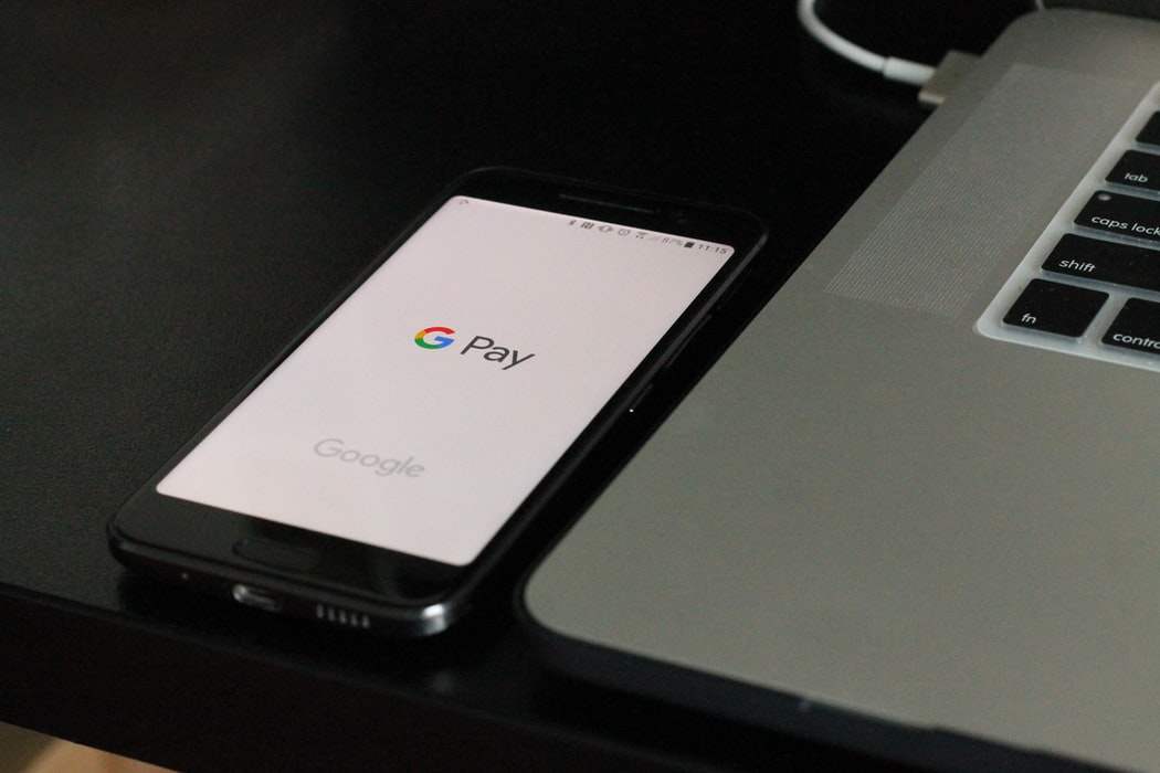 g pay displayed on a phone next to a computer