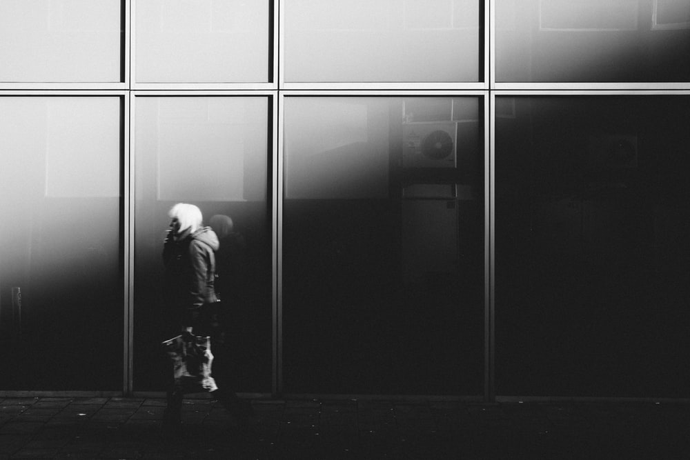 grayscale photography of person walking near glass window building