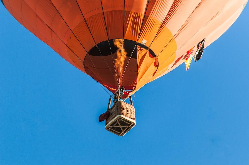 person riding a orange hot air balloon
